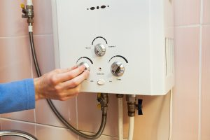 Man's hand regulating the power of a hot water cylinder machine